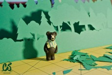 The back bear supervising the woods growing from green paper