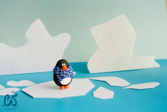 An Adélie penguin brooch sits on an ice sheet before diving
